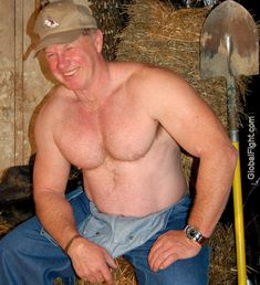 smiling farmer rancher man leaning on hay bales