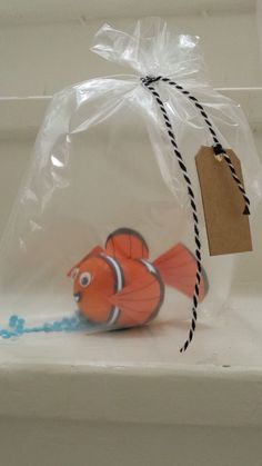 Nemo van mandarijn, Nemo of a tangerine. An easy healthy treat. Using white and orange paper, black marker, little eyes (wiebeloogjes) and duplex tape (dubbelzijdig tape) (No scotch tape (plakband), no glue. That won't work) . A freezer bag (diepvrieszakje) filled with air and some blue confetti, a string and a name label completes it.