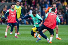 Lionel Messi of FC Barcelona duels for the ball with his teammate Martin Montoya during a training session at the Mini Stadi Stadium on January 3, 2014 in Barcelona, Catalonia.