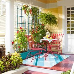 I'm in LOVE!!  This is what I want the porch to look like.  !. trellis planter box for privacy, 2.  fresh painted patio furniture, 3. hanging plants, 4. bright carpet to tie it all together.