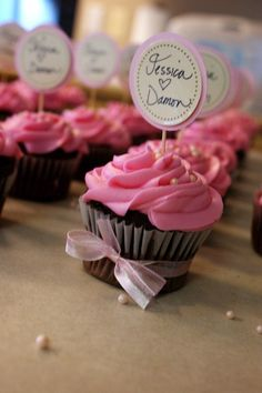 We should put bows on the cupcakes. Very cost efficient. What do you think of the name on top of them?