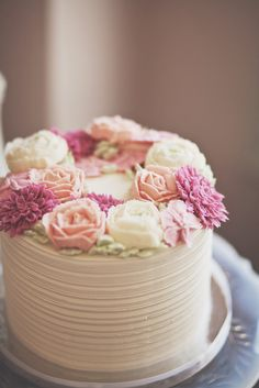 Rustic buttercream cake with soft pink and cream rose flowers.