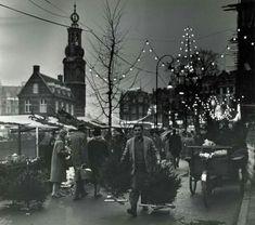 Bloemenmarkt aan het Singel te Amsterdam tijdens kerst. In de kramen/stallen worden kerstbomen verkocht. Op de achtergrond de Munttoren, op de voorgrond een man die in ieders hand een kerstboom vasthoudt. Nederland, december 1966.