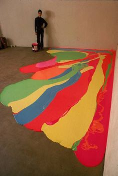 Artist Lynda Benglis painting a floor with 40 gallons of bright latex and pigments at the University of Rhode Island. 1969.
