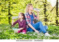 Two sisters drinking water on summer day in park