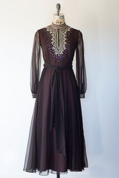 Vintage 1960s black sheer layered maxi with dark wine colored under layer. Dress has long sheer sleeves, back zipper, high mock neck and beautiful