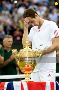 Andy Murray of Great Britain reacts while holding the runners up trophy after being defeated in his Gentlemen's Singles final match against Roger Federer of Switzerland on day thirteen of the Wimbledon Lawn Tennis Championships at the All England Lawn Tennis and Croquet Club on July 8, 2012 in London, England.