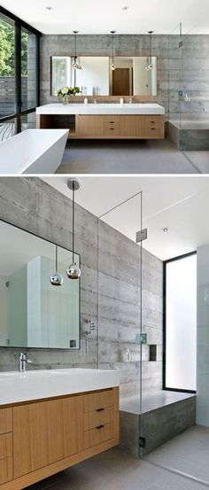 In this modern bathroom the concrete walls and details like the white standalone tub floating double vanity with ample storage and large backlit mirror give the bathroom a contemporary feel while at the same time give it a warm and inviting look. In the shower there's a large concrete bench to match the concrete walls and a glass shower screen keeps the vanity dry.