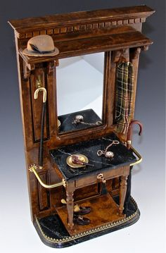 wonderful hall tree... camel fedora, Burberry type scarf, pipe, watch with fob. The table is black marble as well as the umbrella and walking stick areas. The base displays a pair of stylish men's shoes and has a brass gallery.