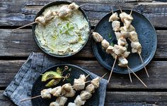 Chicken skewers with baked artichoke and white cheese dip