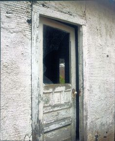 Door, once opening on a home, yawns abandoned