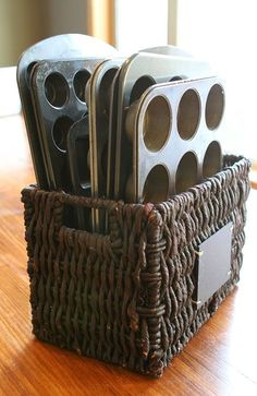 Idea para almacenaje de moldes repostería - Store your cupcake and muffin pans in magazine baskets. Kitchen Pantry Organization!