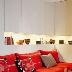 Banquette rouge avec derrière une longue niche horizontale éclairée et des placards blancs
