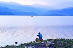 View of the mountains and a child playing by the Lake Fewa near Lakeside the touristic area of Pokhara, Nepal.
