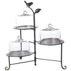 """Three-tier metal dessert stand with three glass domes.    Product: 3 Tier cake stand    Construction Material: Metal and glass Color: Black   Features:Movable traysThree tiersGlass domes included     Dimensions: 19"""" H"""