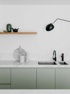 Küche mit minimalistischem Design, weiße Marmortischplatte, Marmorschneidebrett, grüne Küchenschranktüren