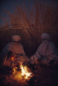 Tuareg goatherds drink tea in their desert shelter at Hassi Izernene, August 1973.  Photograph by Thomas J. Abercrombie, National Geographic