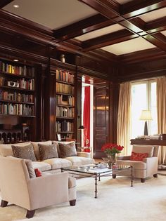 Coffered ceilings add elegance. The grace of this mahogany-panelled library is accentuated by the clean lines of the silk-upholstered sofa and velour chairs.