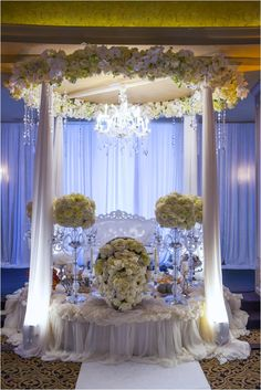 Wedding ceremony alter accented with flowers and a chandelier ~ Photo: John Ly Photography