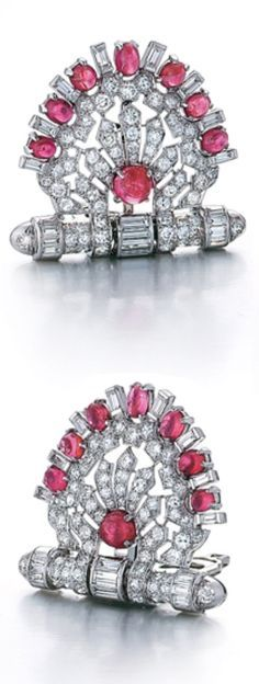A Pair of Art Deco Diamond and Ruby Clips, Circa 1935. Each shaped as a semi-circular openwork fan set with round cut diamonds and centred with a cabochon ruby, the edges set with baguette diamonds alternating with cabochon rubies, all rising from a bar set with baguette and round cut diamonds.