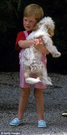 Pictured: Prince Harry cuddling a dog while on holiday in Majorca in 1987