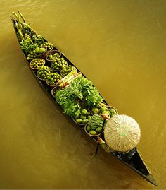 Beautiful shot of a farmer with his produce arranged on his small boat on the Mekong in Vietnam, heading off to the morning market