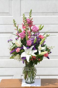 Lavender, pink and white flowers including Roses and lilies. Arranged by your local Riverside Florist - Willow Branch Florist of Riverside