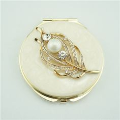 Pearl feather design metal compact mirror This decorated compact mirror is a perfect gift for lady. It is covered with ivory enamel glaze and mounted with bling-bling crystals and elegant pearls. There are two mirrors inside.
