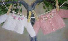 Two hand knit and embroidered doll sweaters.