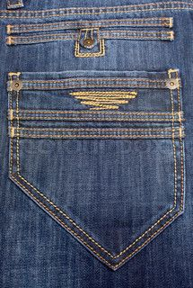 big back pocket on jeans with a yellow embroidery