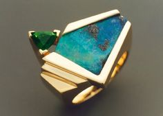 This large, 14k gold woman's ring features a beautiful piece of Boulder Opal accented with a trillion cut Chrome Tourmaline (the color of the Tourmaline is a much brighter green than shown in the photo). The ring is approximately 23 mm across the top, weighs 16.3 grams, and is a size 6.5. It's size can be slightly adjusted up or down, and this is done free of charge.  $2400.00
