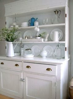 Open white cabinetry and vintage finds