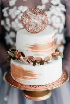 A simple, chic, white cake from La Petite Patisserie was giving a modern make-over, brushed with rugged, copper strokes and adorned with copper sprayed eucalyptus. The spherical topper? We LOVE it! http://www.confettidaydreams.com/copper-metallic-and-blush-wedding-ideas/