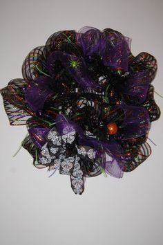 This wreath is 29 inches around . It is made with black deco mesh with orange, green, and purple stripes. There are purple and green tube