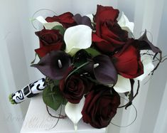 "This calla bridal bouquet is an elegant presentation style wedding bouquet. The callas lilies are soft to touch and look so real, you are sure to love them. There are 12 dark plum purple & white mini calla lilies in this bouquet, 7 black baccara red velvet touch roses, added bear grass, and willow to make this a classy presentation ( one sided ) bouquet. Each lily bloom measures 2"" by 3"". Handle treatment is wrapped with velvet damask ribbon & a black satin sash, completed wit…"