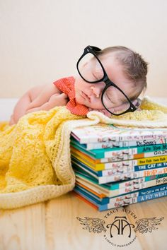 cute newborn photo idea - baby in glasses sleeping on a stack of Dr. Seuss books!