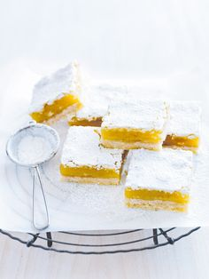lemon slice 1 cup (220g) caster (superfine) sugar 1 cup (80g) desiccated coconut 2 cups (300g) plain (all-purpose) flour 200g unsalted butter, melted icing (confectioner's) sugar, for dusting lemon filling 4 eggs 2 egg yolks, extra 2 cups (440g) caster (superfine) sugar ⅓ cup (50g) plain (all-purpose) flour, sifted 1 tablespoon finely grated lemon rind 1 cup (250ml) lemon juice (see tip)