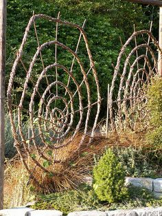 Well Gardens: Woven Spiral Wall Chalice Well Gardens: Woven spiral garden structures looks sorta like a Spider web!Chalice Well Gardens: Woven spiral garden structures looks sorta like a Spider web! Spiral Garden, Garden Trellis, Witch's Garden, Garden Sheds, Wall Trellis, Diy Trellis, Garden Whimsy, Cheap Trellis, Garden Privacy