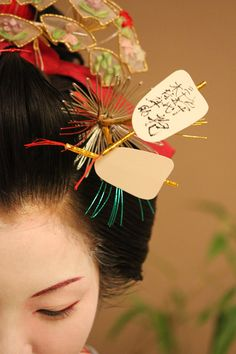 "Kanzashi (ornament hairpin) in the shape of a sumo's referee fan. ""I asked the 35th Shohnosuke Kimura, one of the top Gyoujis, to sign his autograph on my kanzashi, a ornament hairpin, with all due respect. This kanzashi is the shape of a gunbai, the referee's fan, which is made by my brother-geisha, Kikuzi."" - Kikuhina"