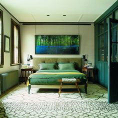 Jonathan Reed's London former coach house. A 2005 photograph by Chrystel Lebas from her 'Blue Hour' series hangs above the suede headboard. The hexagonal bedside tables are by Robert Lorimer, and the steel reading lights are by Studio Reed. To the right is the dressing room, separated by a screen designed by Plain English and Jonathan Reed. Photography: Simon Upton.