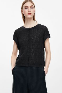 This sleeveless cardigan is a lightweight style with a textured, slightly sheer, boucle knit. Loosely fitting and slightly cropped, it has hidden press buttons, a round neckline and tightly ribbed cuffs and hem.