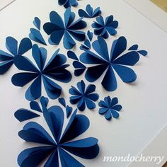 hearts folded in half with one side taped down in a circular pattern...cute idea for wrapping paper