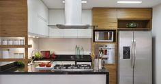 Cozinha com coifa metálica e armários de madeira