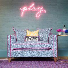 Handwritten pink neon sign reading 'play', Phillip Jeffries teal grasscloth walls, blue leopard print velvet snuggler armchair with pink velvet piping