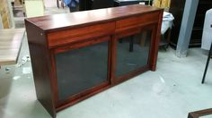 live edge buffet / cabinet with sliding doors and black metal mesh.  Built with ambrosia maple and finished in a red cherry tone