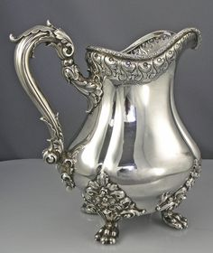 An American antique sterling silver pitcher with a hand engraved crest on the side and ornate applied cast claw feet. Ornate chased rim and handle.