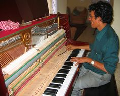 Khaleel, a piano tuner based in Bangalore, at work.    You can see a closer view of the piano strings and dampers in these two pictures. pic1 and pic2     Learn how to play the piano and bring|add joy|hapiness to your life|friends|family