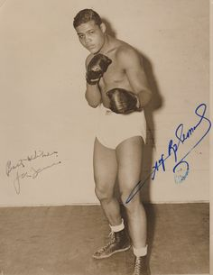 LOUIS JOE: (1914-1981) American Boxer, World Heavyweight Champion 1937-49. Vintage signed sepia 7 x 9 photograph of Louis standing in a full length boxing pose. The original press photograph is signed by Louis in fountain pen ink across a clear area of the image. Curiously the photograph has also been signed in bold blue ink by Sugar Ray Leonard (1956- ) American Boxer, a World Champion in five different weight divisions.