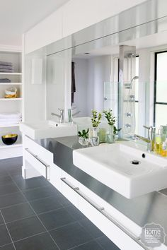 In this bathroom, twin sinks float atop a vanity - surfaced in immaculate stainless steel - against a mirror wall.