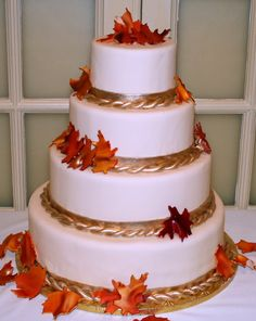 Simple white round layered cake with gold rope, would be beautiful with navy accents, nautical topper